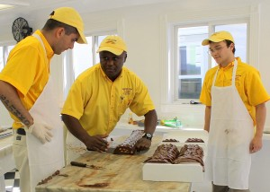 Carnel trains new summer employees how to accurately slice Murdick's fudge.
