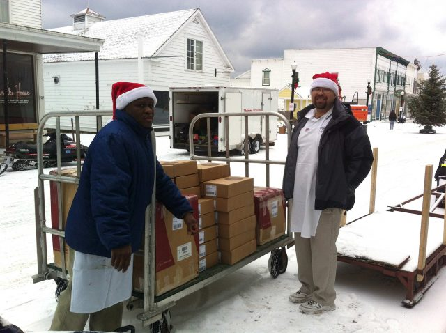 Fudge makers Carnel and Ricardo fill a luggage cart full of Murdick's of Mackinac headed for the Arnold Line dock and FedEx delivery.